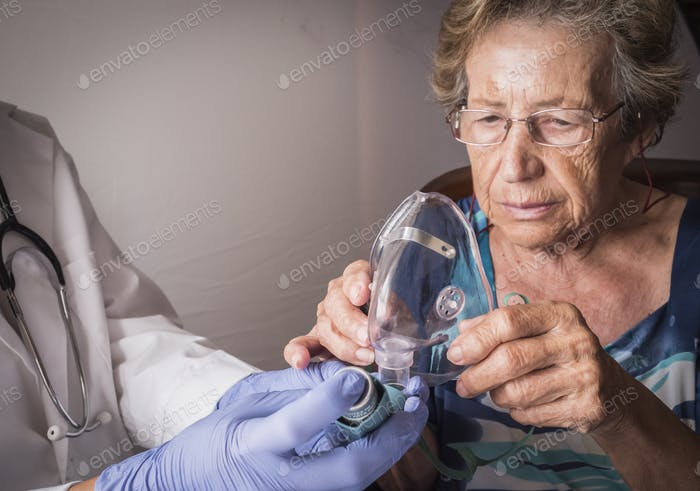Doctor explains to old woman how ventimask inhalation training works