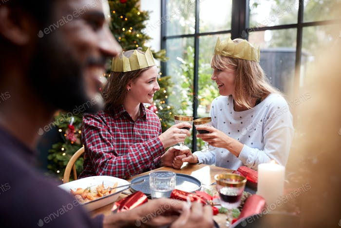 Gay Female Couple Sitting Around Table Making A Toast At Home And Eating Christmas Dinner