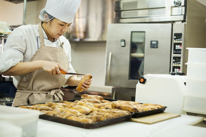 Woman wearing chef's hat and apron working in a bakery, slicing freshly baked rolls on large trays.