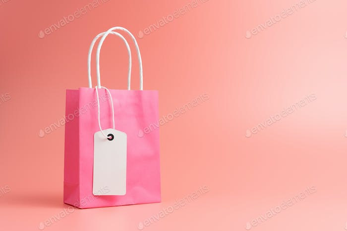 Single pink shopping or gift bag isolated on pink background