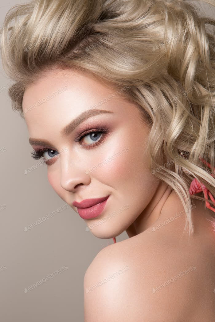 Glamour portrait of beautiful girl model with makeup and romantic wavy hairstyle.