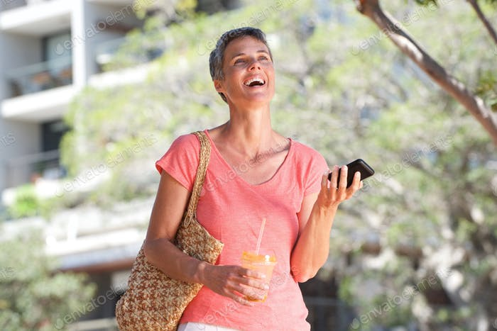 happy woman walking outdoors with drink and mobile phone