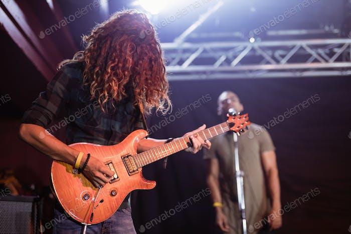 Männlicher Gitarrist, der im Nachtclub auftritt