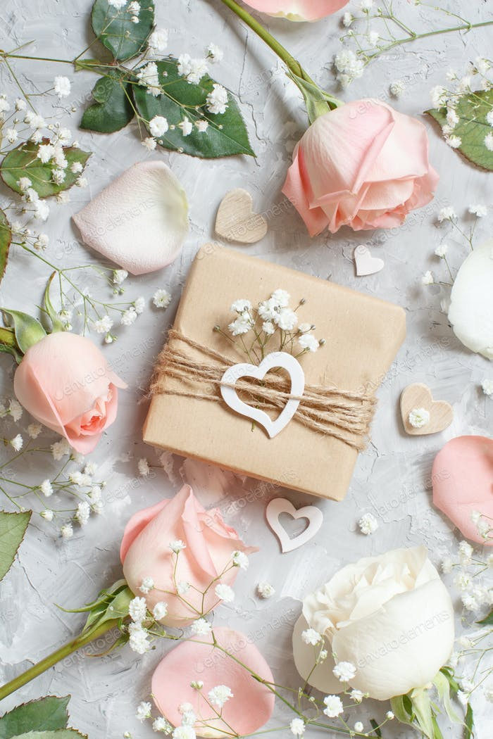 Gift box with roses and small white flowers