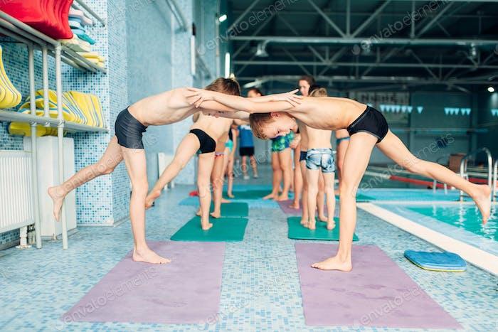 Jungen machen sportliche Übungen in Paaren in der Nähe von Pool.