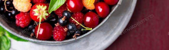 Banner von Mix Obst und Beeren in grauer Metallschale auf rotem Hintergrund.