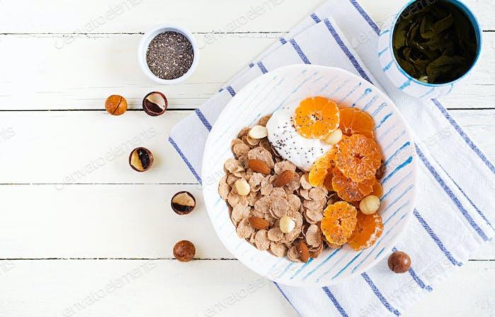 Schüssel mit Flocken mit Joghurt und Mandarine auf weißem Holztisch.
