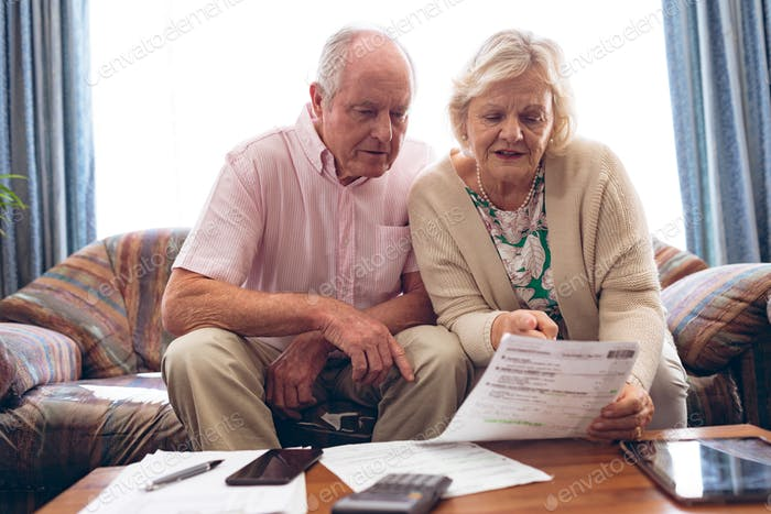 Couple discussing over medical bill while sitting on vintage sofa at retirement home