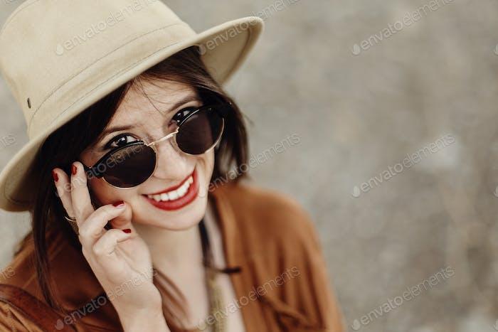 stilvolle Boho Frau in Sonnenbrille hält Hut, mit windigen Haaren