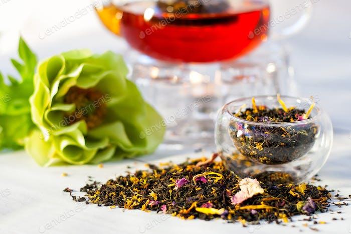 schwarzer Tee mit geschnittenen Blumen und Teekanne