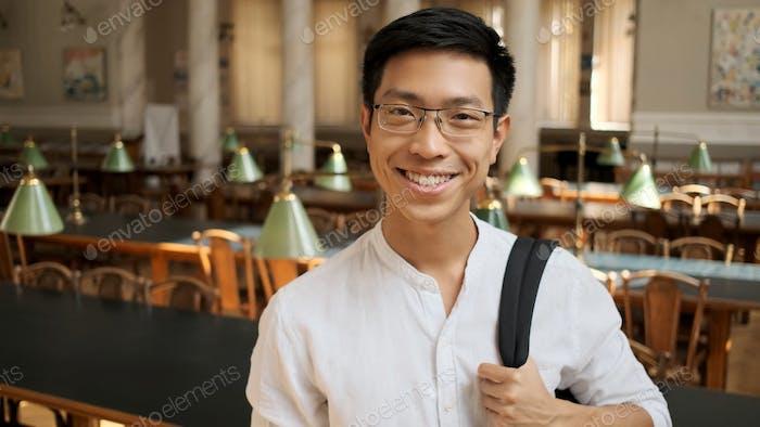 Fröhliche asiatische Student mit Rucksack glücklich suchen in der Kamera in der Bibliothek. Glücklicher Ausdruck