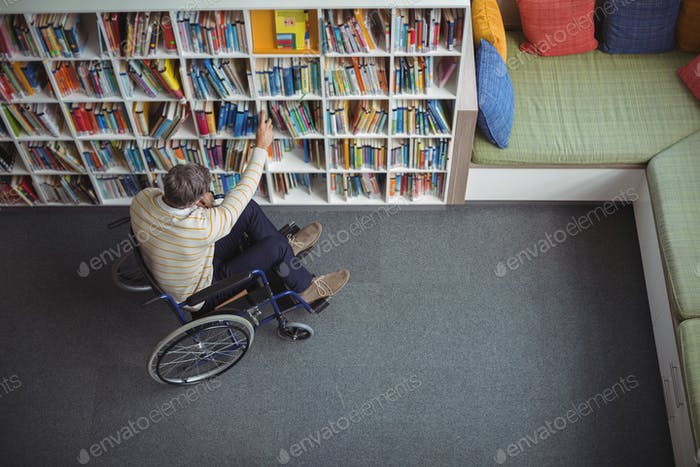 Overhead view of disabled school teacher selecting book in library