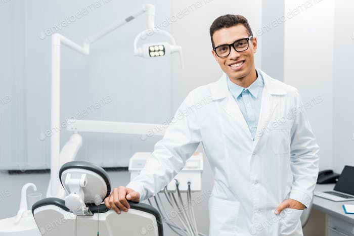 handsome african american dentist smiling and standing with hand in pocket