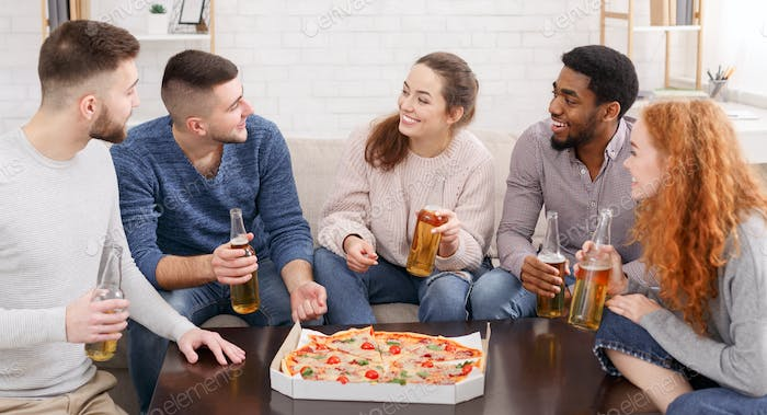 Young multiethnic friends with pizza celebrating meeting at home