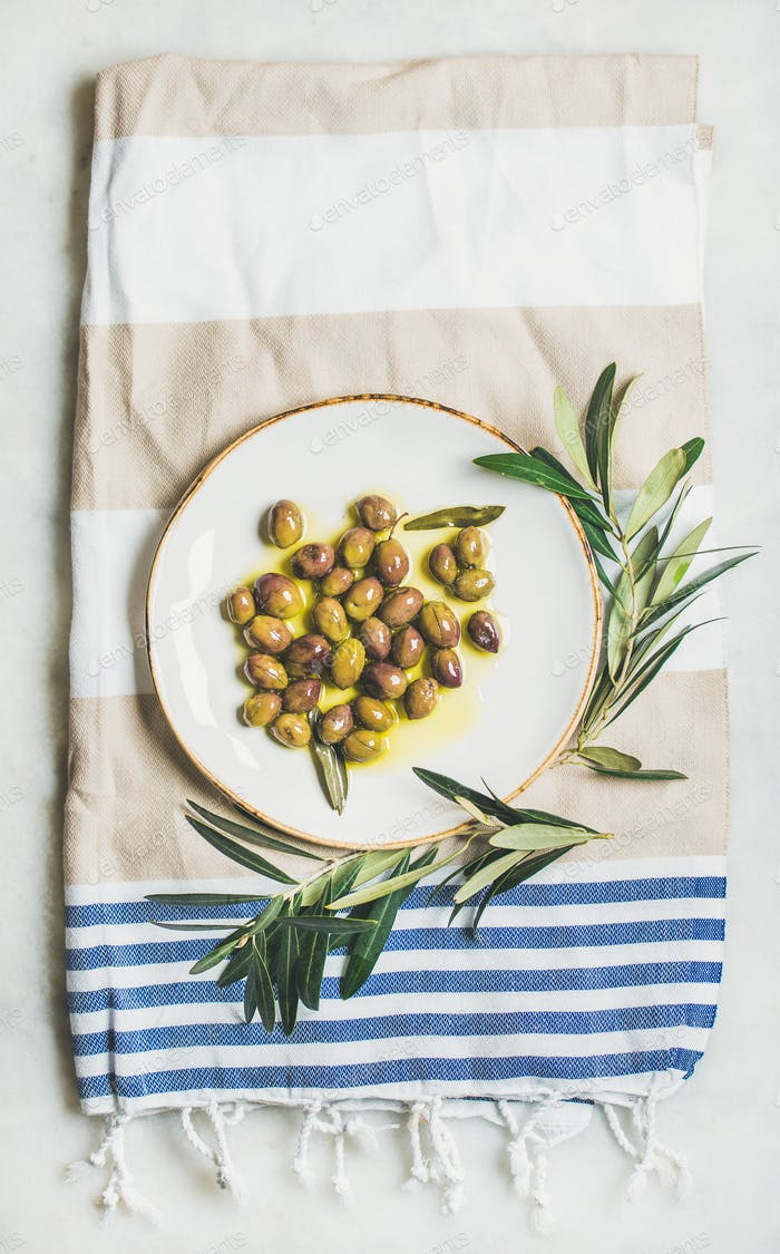 Pickled green Mediterranean olives on white ceramic plate, top view