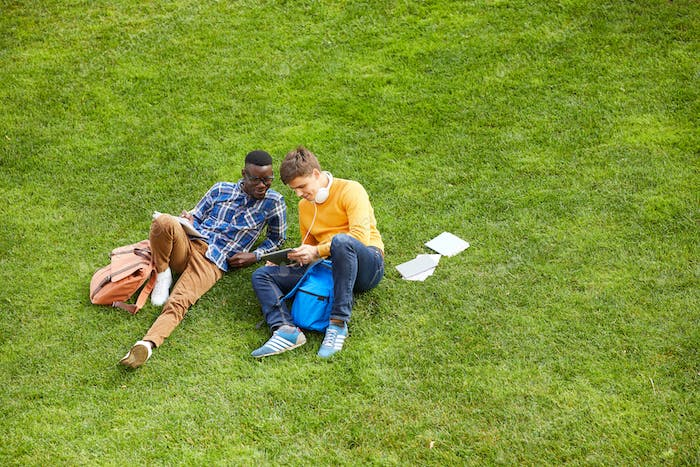 Students Relaxing on Green Grass