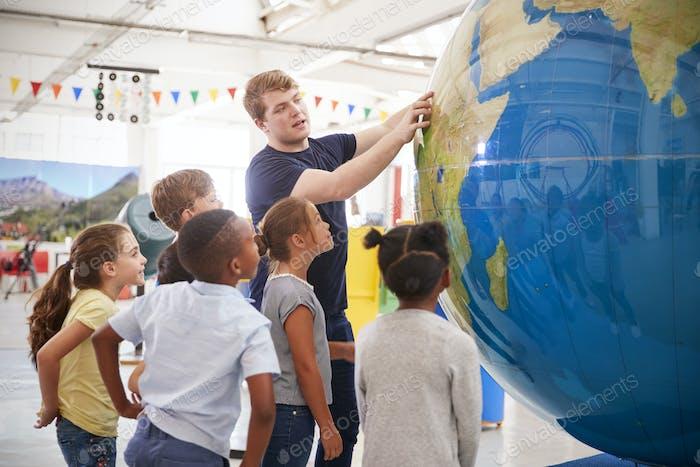 Kinderuhrpräsentation mit riesigem Globus in einem Wissenschaftszentrum