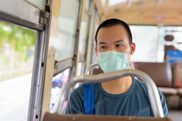 Face of young Asian man with mask riding the bus with distance