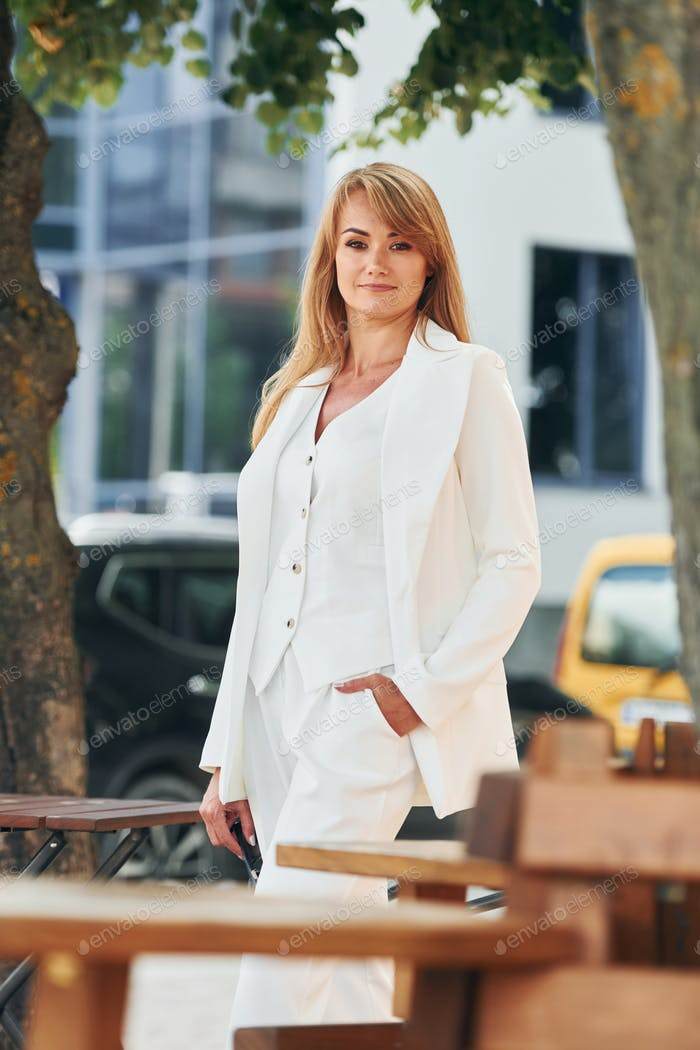 Near table. Woman in formal wear standing outdoors in the city at daytime