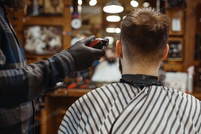 Парикмахерская в шляпе стрижет волосы клиента, парикмахерская