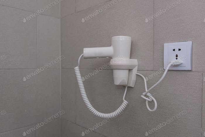 Hair dryer hanging on wall in bathroom