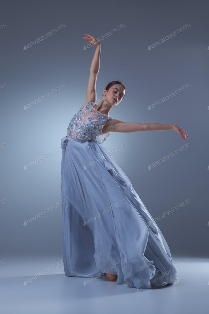 The beautiful ballerina dancing in blue long dress