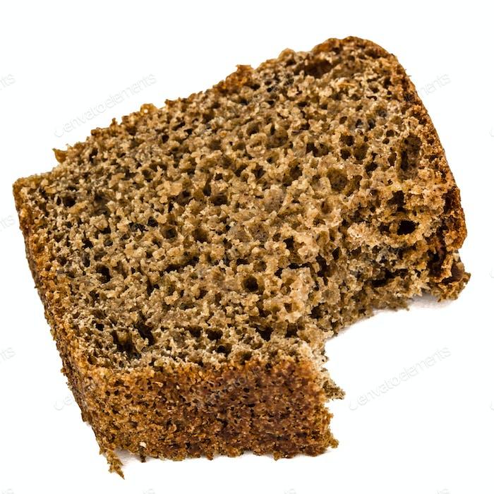 Bitten slice of bread made of dark flour, isolated on white back