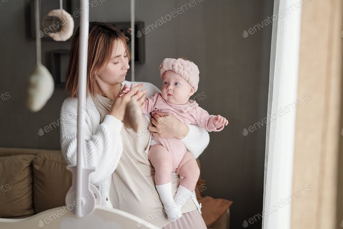 Young careful mother looking at her adorable baby daughter