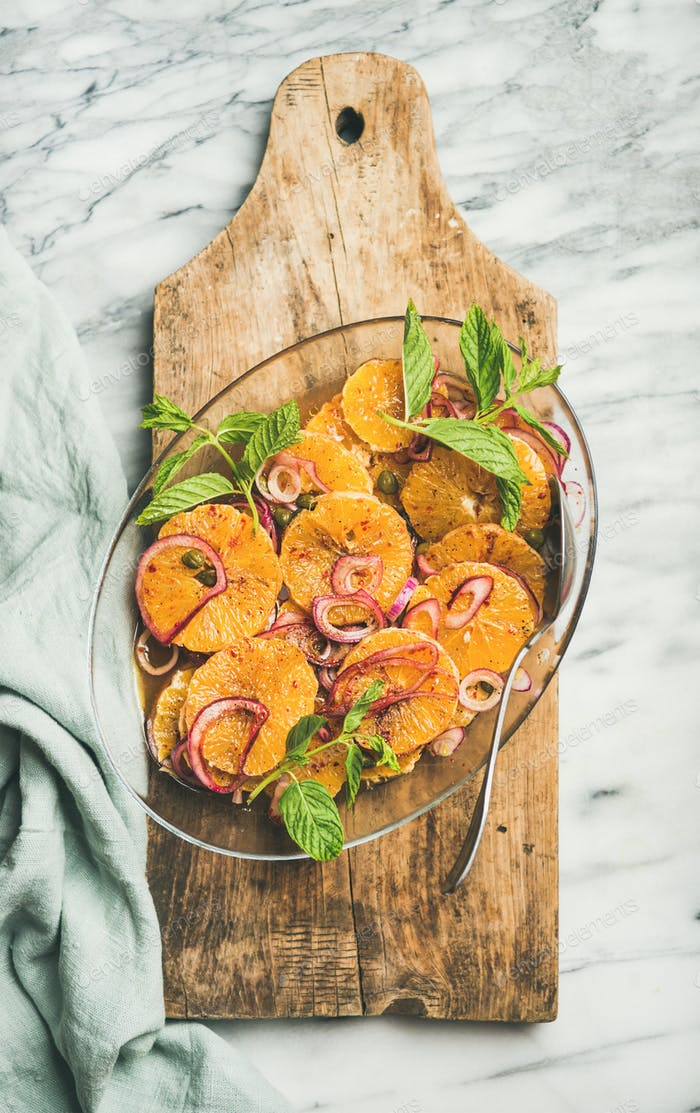 Flat-lay of orange, pickled onion and caper salad on board