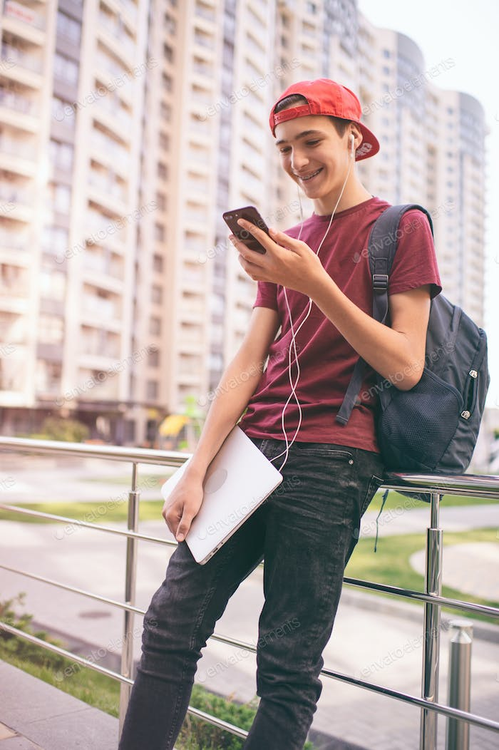 Smiling teenager  looks to the cell phone screen, in the city.