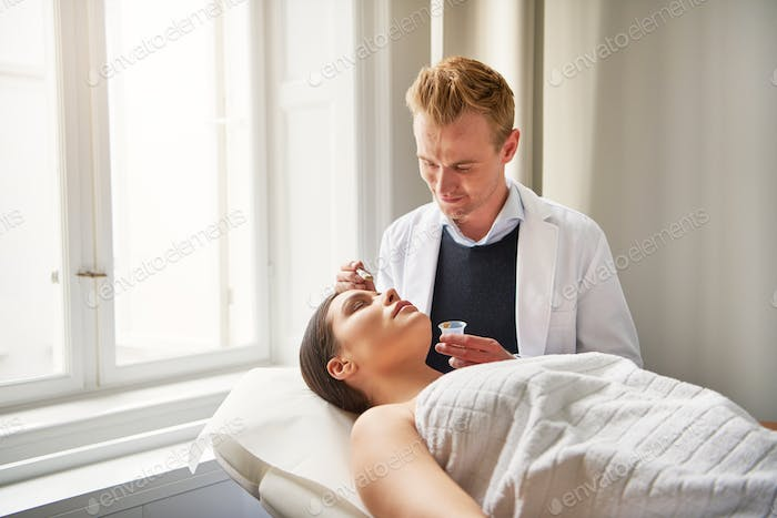 Beauty specialist applying mask on female client face