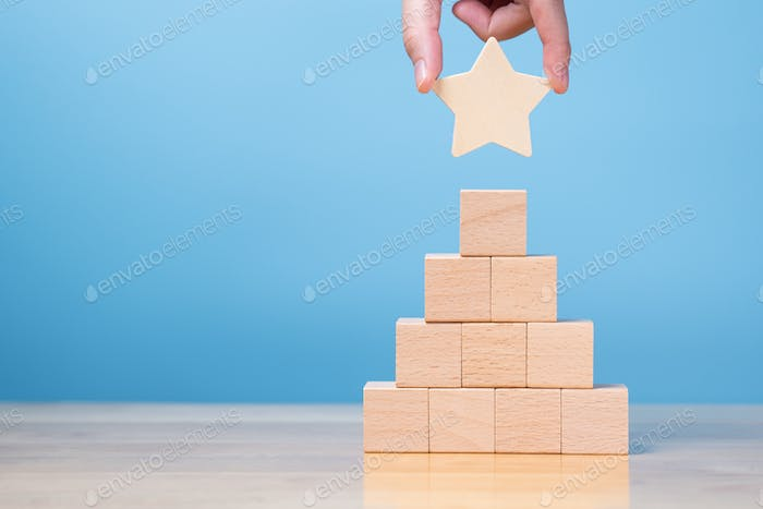 hand putting star on wood block