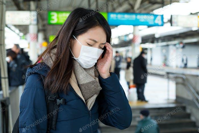 Woman feeling dizzy at train platform