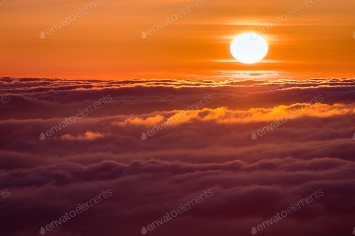 Bright sunlight reflected on a sea of clouds before sunset