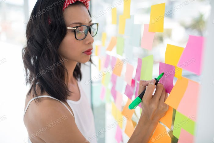 Female executive writing on sticky notes