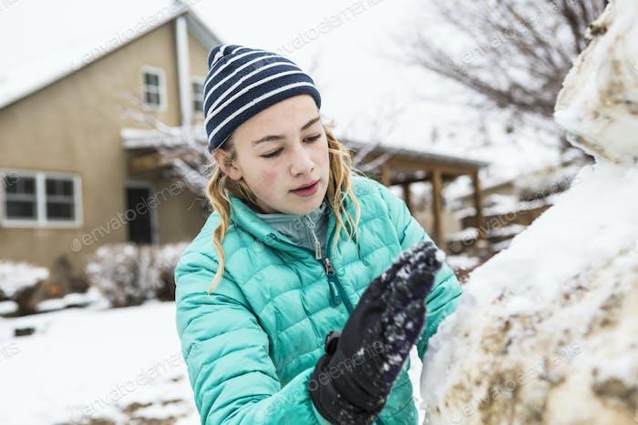 Dreizehn Jahre altes Teenager-Mädchen bauen einen Schneemann
