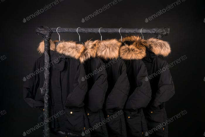 lot of black coats, jacket with fur on hood hanging  clothes rack.  background.