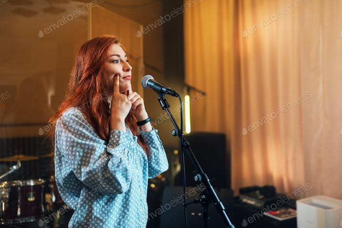 girl does exercises with lips at chants in vocal lesson near the microphone