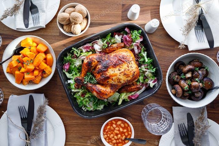 Draufsicht des dekorierten festlichen Tisches mit ganzen gebratenen Hühnchen