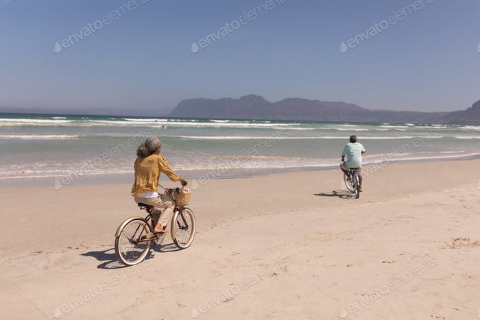 Rear view of senior couple riding bicycle on beach in the sunshine with mountains in the background