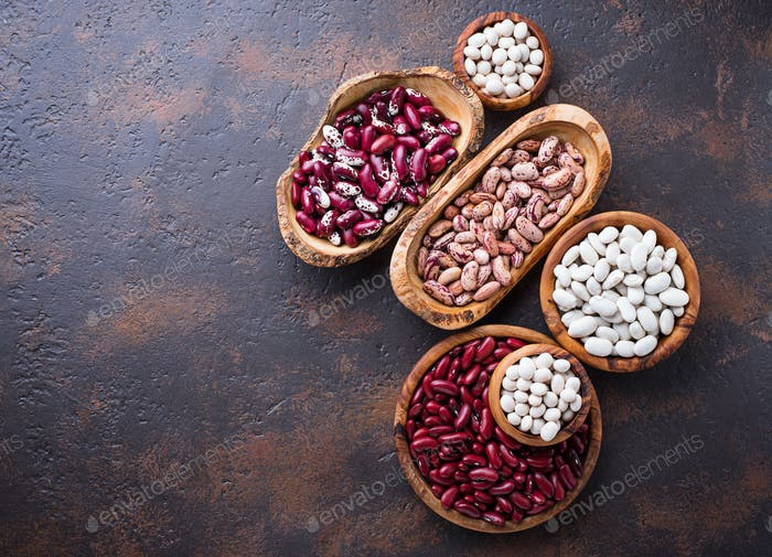 Assortment of various beans in wooden bowls