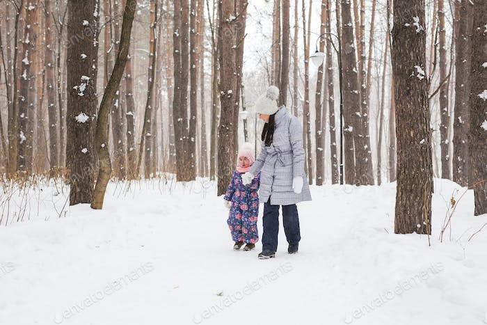 Winter, childhood and people concept - mother is walking with her little daughter in snowy forest