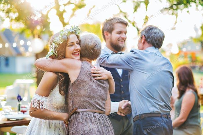 Los invitados felicitan a la novia y el novio en la recepción de la Boda fuera en el patio trasero.