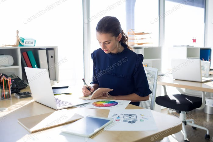 Female executive writing in diary at her desk