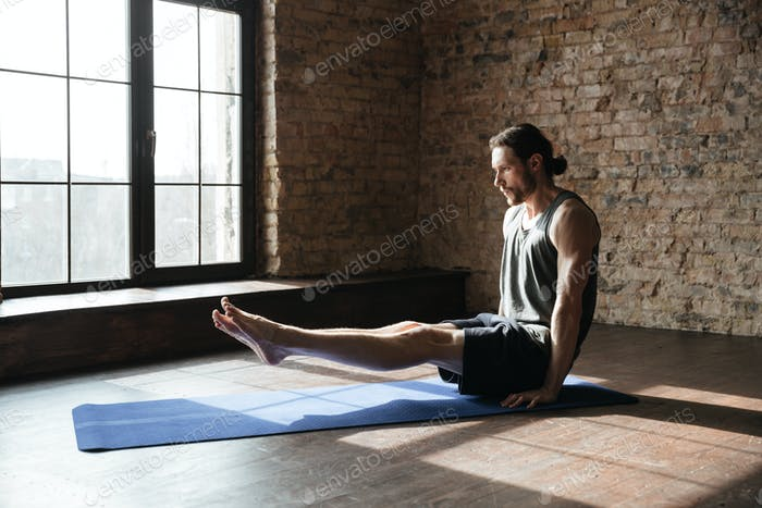 Concentrated strong sportsman in gym make yoga sport exercises