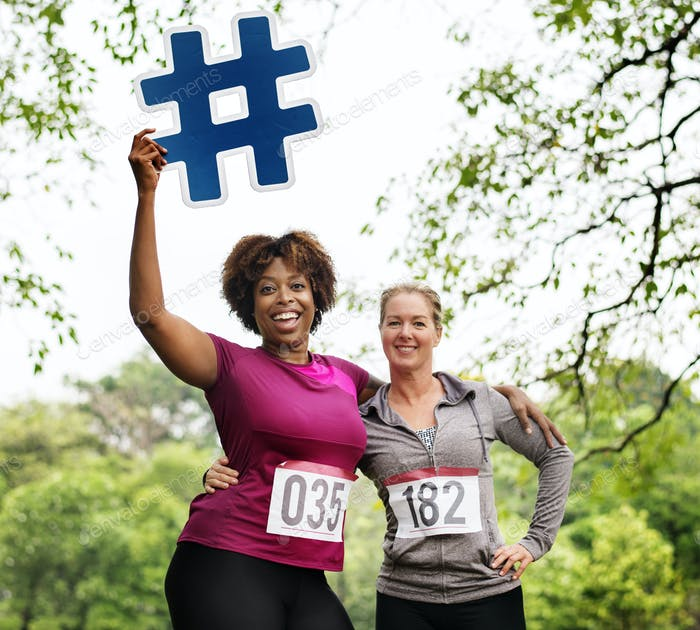 Diverse women with hashtag icon in the park