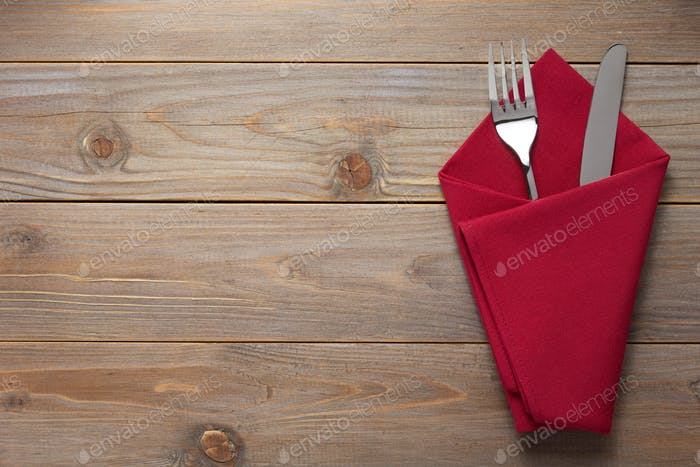 knife and fork in napkin at rustic wooden background