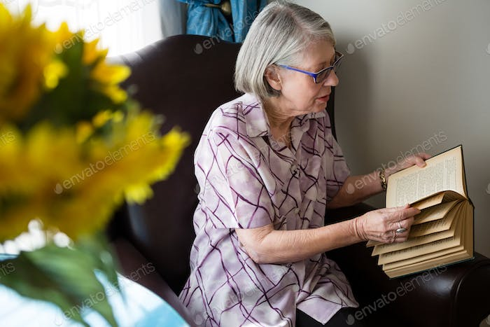 Senior woman reading book while sitting in nursing home
