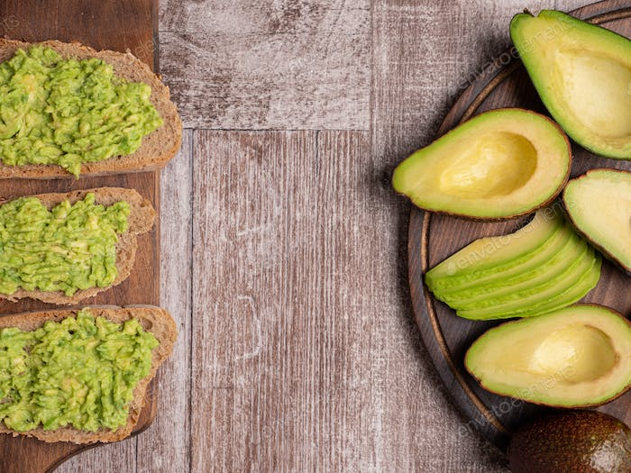 Fresh sandwiches made with avocado on a wooden board