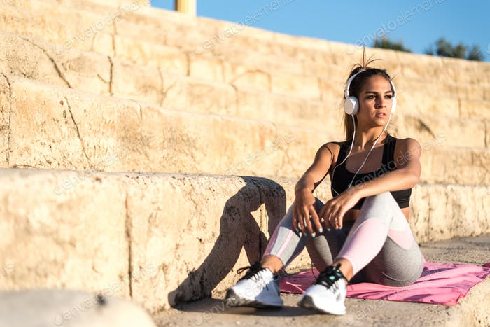 sports woman outdoor in a stairs resting after doing exercise listening music